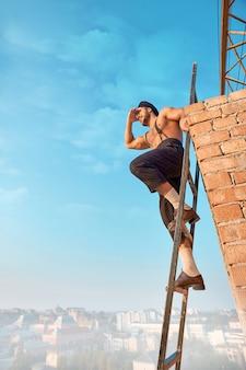 Construtor encostado na parede de tijolos e sentado na escada no alto. macho com torso nu em roupa de trabalho segurando a mão perto dos olhos e olhando para longe. paisagem urbana em segundo plano.