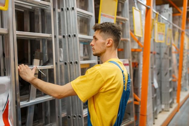 Construtor escolhendo as escadas em loja de ferragens