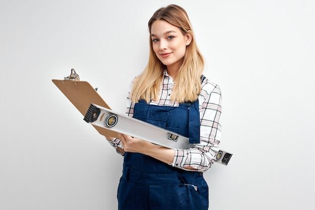 Construtor feminino de uniforme azul segurando o equipamento e a prancheta de papel nas mãos, posando para a câmera sorrindo. retrato