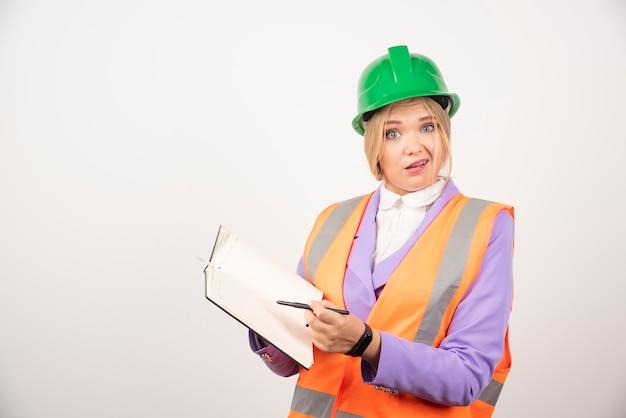 Construtor feminino no capacete com tablet na parede branca.