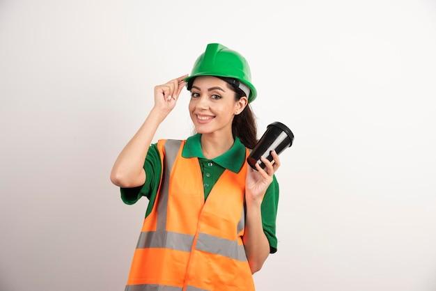Construtor feminino sorridente com copo preto. foto de alta qualidade