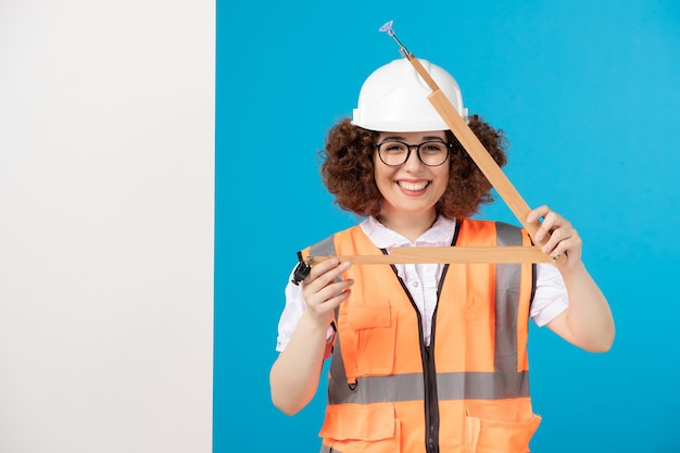 Construtor feminino sorridente de vista frontal de uniforme com ferramenta de madeira em azul
