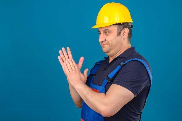 Construtor homem envelhecido médio vestindo uniforme de construção e capacete de segurança, esfregando as palmas das mãos e sorrindo olhando confiante sobre parede azul isolada