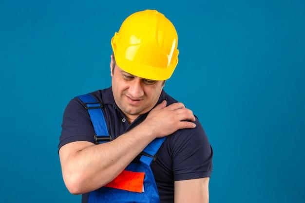 Construtor homem envelhecido médio vestindo uniforme de construção e capacete de segurança tocando o ombro com dor sobre parede azul isolada