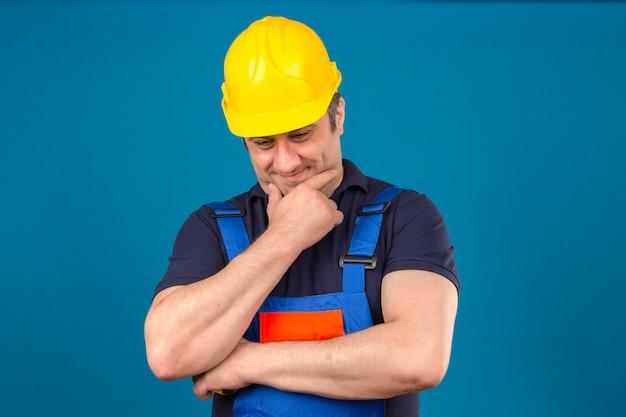 Construtor homem envelhecido médio vestindo uniforme de construção e capacete de segurança tocando o queixo e pensando sobre parede azul isolada