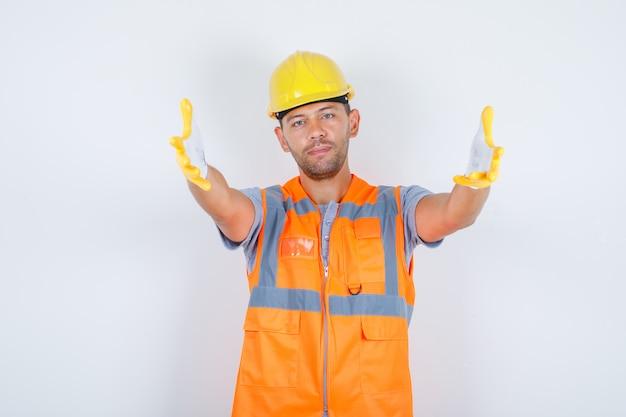 Construtor homem fazendo gesto de passe-me com as mãos no uniforme, capacete, luvas, vista frontal