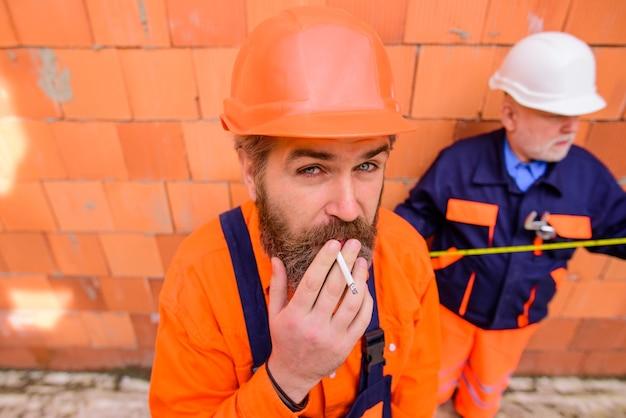 Construtor homem trabalhador da construção civil fumando retrato de bonito engenheiro barbudo relaxa por