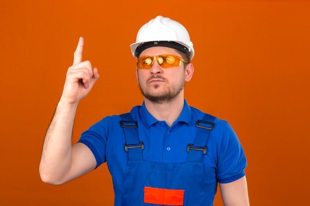 Construtor homem vestindo uniforme de construção e capacete de segurança adverte de perigo, levantando o dedo mostrando sinal de aviso com o dedo em pé sobre parede laranja isolada