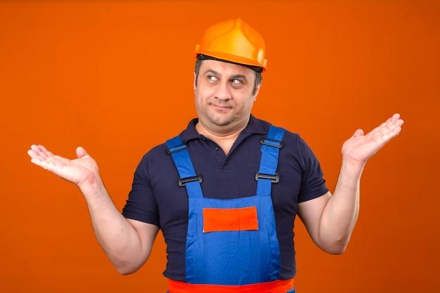 Construtor homem vestindo uniforme de construção e capacete de segurança, encolher os ombros os ombros, espalhando as mãos, não entendendo o que aconteceu sem noção e expressão confusa sobre a parte traseira laranja isolada