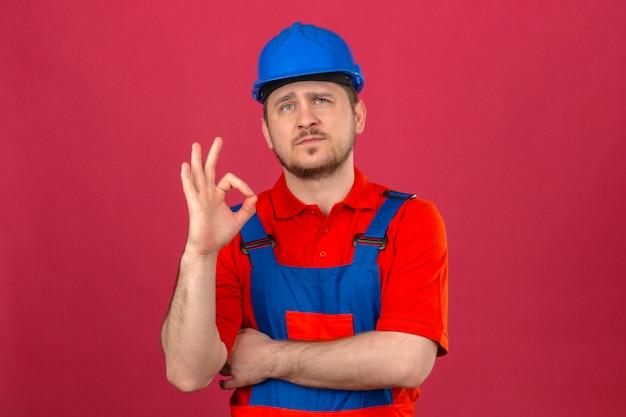 Construtor homem vestindo uniforme de construção e capacete de segurança, olhando com olhar sonhador, fazendo sinal de ok em pé isolado parede rosa