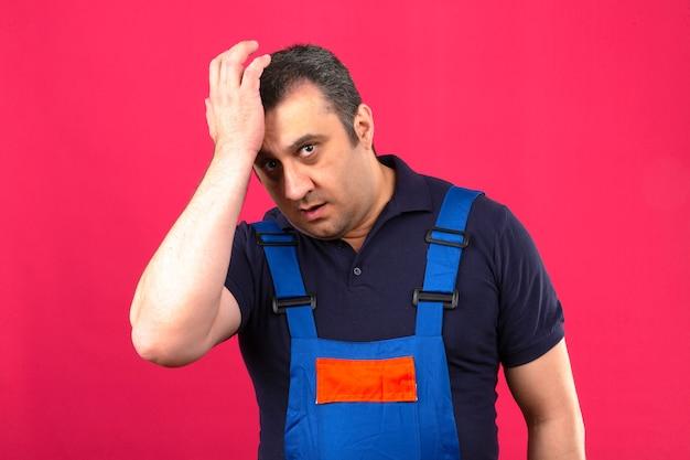 Construtor homem vestindo uniforme de construção em pé surpreso com a mão na cabeça por erro conceito de memória ruim sobre parede rosa isolada