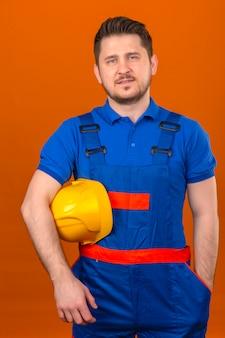 Construtor homem vestindo uniforme de construção permanente com capacete de segurança na mão com sorriso confiante sobre parede laranja isolada