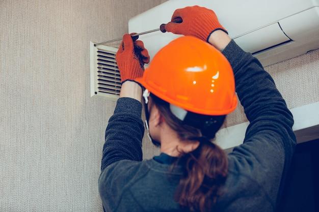 Construtor industrial, faz-tudo instalando porta-filtro de ventilação ou ar condicionado na parede. ocupação de técnico, reparador ou engenheiro em trajes de trabalho de proteção durante o trabalho diário.