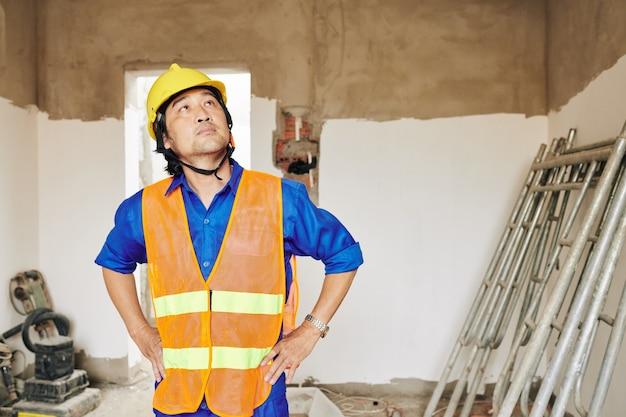 Construtor insatisfeito e pensativo olhando para manchas de água no teto e planejando consertar o telhado com vazamento