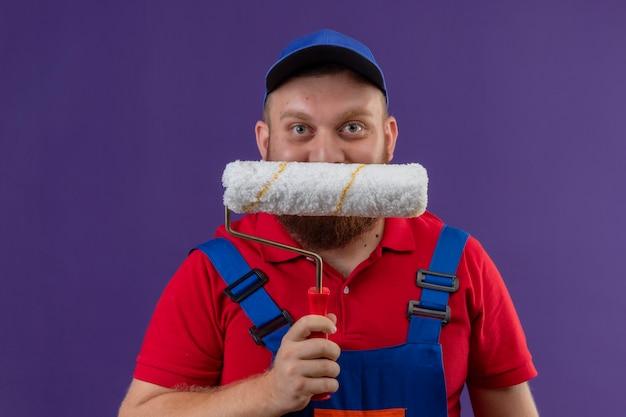 Construtor jovem barbudo com uniforme de construção e boné escondendo o rosto atrás do rolo de pintura, sorrindo sobre fundo roxo