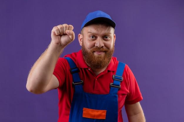 Construtor jovem barbudo com uniforme de construção e boné levantando o punho como um vencedor sorrindo sobre fundo roxo