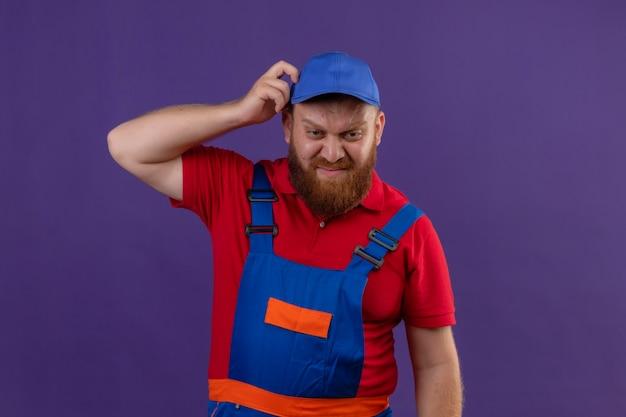 Construtor jovem barbudo, com uniforme de construção e boné, parecendo inseguro e confuso, coçando a cabeça sobre um fundo roxo