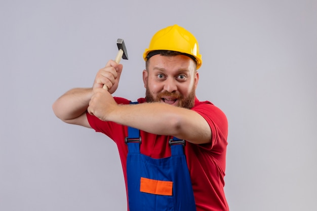 Construtor jovem barbudo com uniforme de construção e capacete de segurança balançando um martelo olhando para a câmera sorrindo