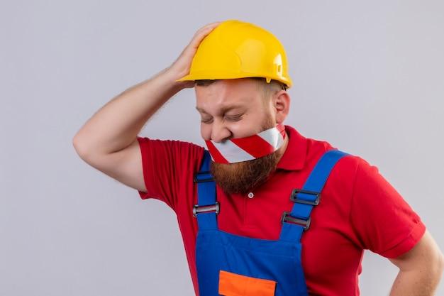 Construtor jovem barbudo com uniforme de construção e capacete de segurança com fita adesiva na boca, parecendo confuso e decepcionado com a mão na cabeça por engano