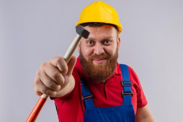 Construtor jovem barbudo com uniforme de construção e capacete de segurança mostrando o martelo para a câmera, olhando para a câmera de forma positiva e feliz