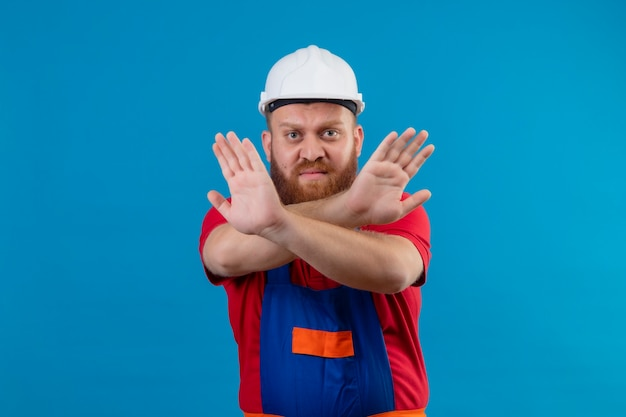Construtor jovem barbudo com uniforme de construção e capacete de segurança olhando para uma câmera preocupada fazendo sinal de pare cruzando as mãos