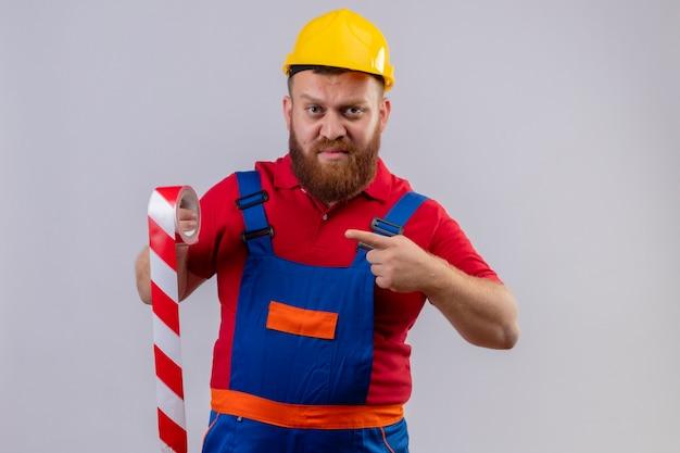Construtor jovem barbudo, com uniforme de construção e capacete de segurança, segurando uma fita adesiva apontando com o dedo para ela, parecendo descontente