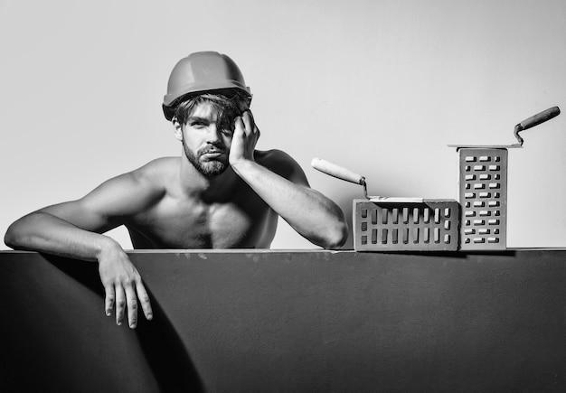 Construtor jovem bonito barbudo cansado machão com corpo forte atlético musculoso sexy tem mãos fortes em capacete laranja ou capacete com tijolo e ferramenta, espaço de cópia