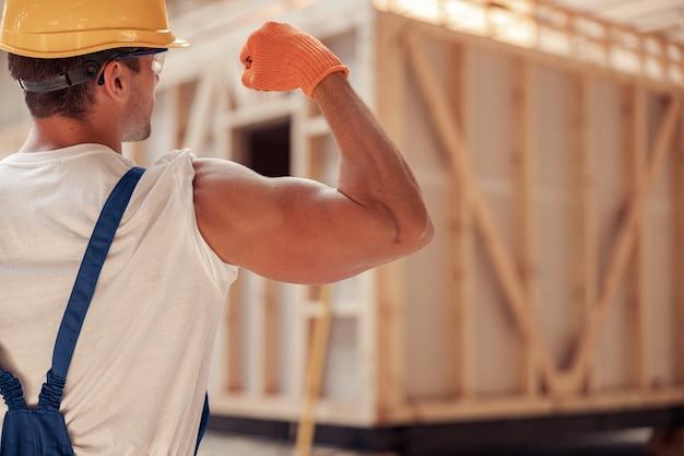Construtor jovem e atlético demonstrando seu braço musculoso
