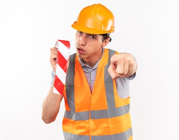 Construtor jovem e rigoroso de uniforme segurando fita adesiva mostrando seu gesto