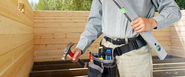 Construtor mantém nível e martelo em casa de madeira de fundo para construção