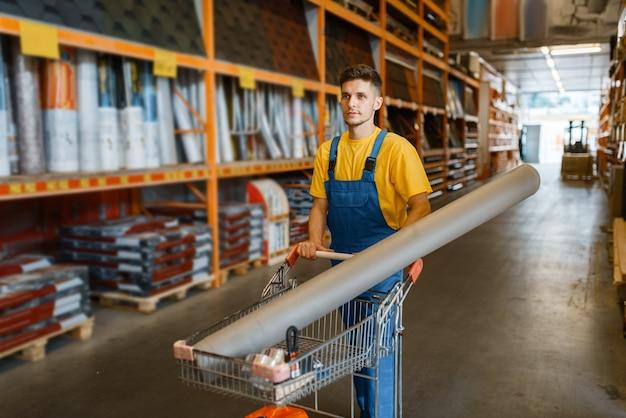 Construtor masculino carrega materiais de construção em um carrinho, loja de ferragens. o cliente olha as mercadorias na loja de bricolagem