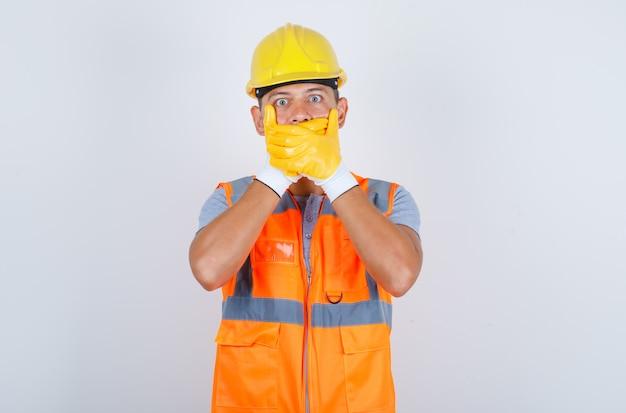 Construtor masculino cobrindo a boca com as mãos por engano no uniforme, capacete, luvas e parecendo chocado, vista frontal