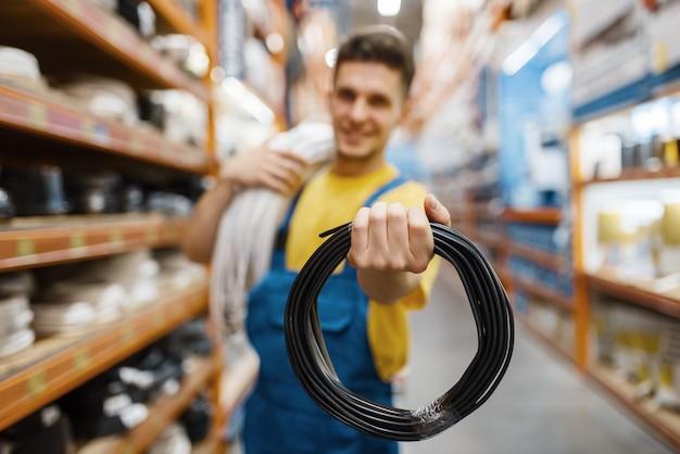 Construtor masculino com bobina de fios em loja de ferragens. construtor de uniforme olha as mercadorias na loja de bricolage