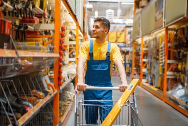 Construtor masculino com carrinho na prateleira da loja de ferragens. construtor de uniforme olha as mercadorias na loja de bricolage
