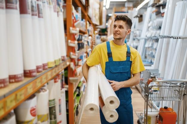 Construtor masculino com rolo de papéis de parede na loja de ferragens. construtor de uniforme olha as mercadorias na loja de bricolage