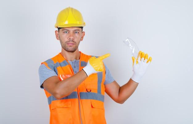 Construtor masculino de uniforme, capacete, luvas apontando óculos de segurança com o dedo, vista frontal.
