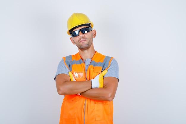 Construtor masculino de uniforme, capacete, luvas, óculos em pé com os braços cruzados e olhando confiante, vista frontal.