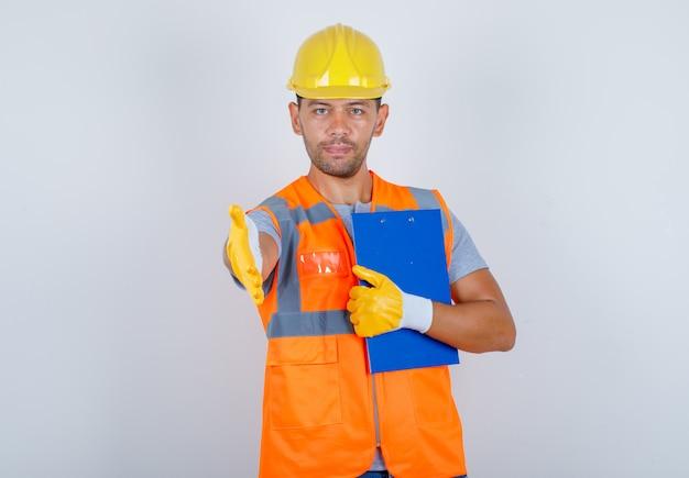 Construtor masculino de uniforme, capacete, luvas, oferecendo um aperto de mão com a prancheta na mão, vista frontal.