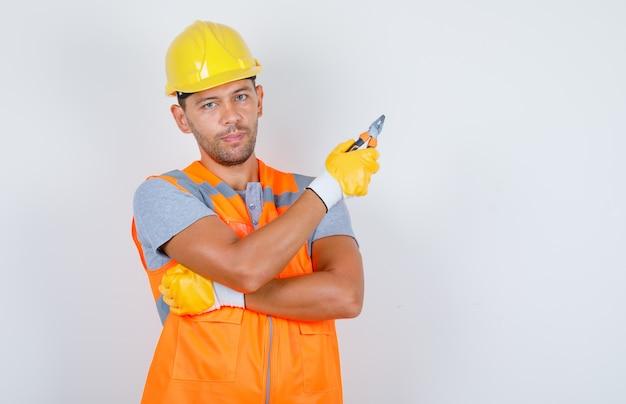 Construtor masculino de uniforme, capacete, luvas segurando um alicate, vista frontal.