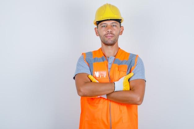 Construtor masculino de uniforme em pé com os braços cruzados e olhando confiante, vista frontal.