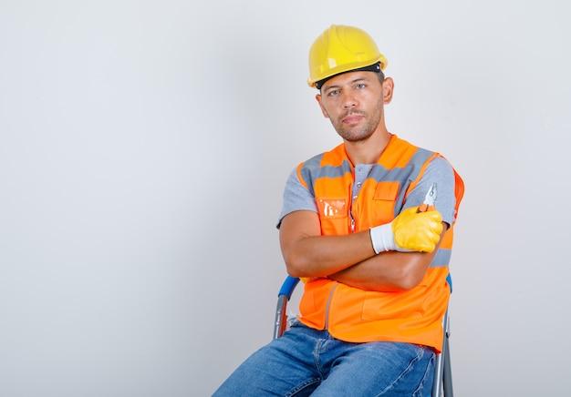Construtor masculino de uniforme, jeans, capacete, luvas, sentado com os braços cruzados, vista frontal.