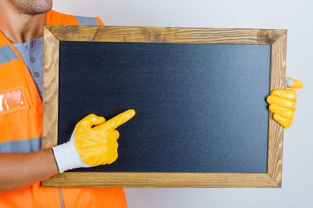 Construtor masculino de uniforme, luvas mostrando algo no quadro-negro, vista frontal.