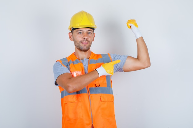 Construtor masculino de uniforme, mostrando seu bíceps com o dedo e parecendo confiante, vista frontal.