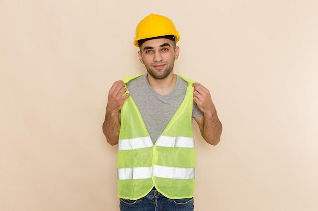Construtor masculino de vista frontal com capacete amarelo em pé com bastante expressão no fundo claro