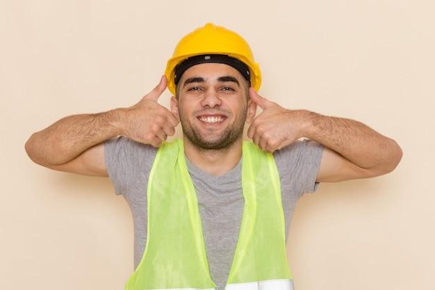 Construtor masculino de vista frontal com capacete amarelo posando como sinal sobre fundo claro