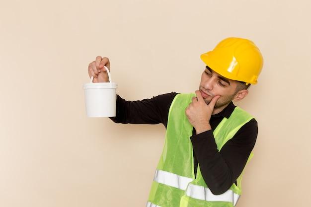Construtor masculino de vista frontal com capacete amarelo segurando tinta com expressão pensativa na mesa de luz