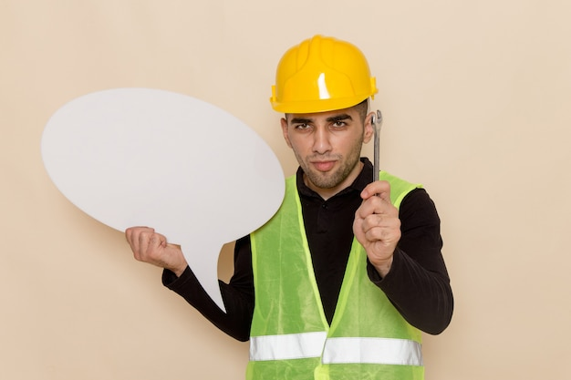 Construtor masculino de vista frontal com capacete amarelo segurando uma placa branca e uma ferramenta sobre fundo creme