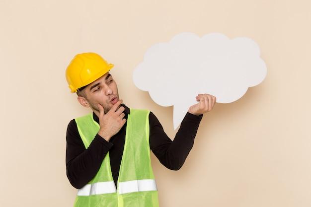 Construtor masculino de vista frontal com capacete amarelo segurando uma placa branca sobre fundo claro