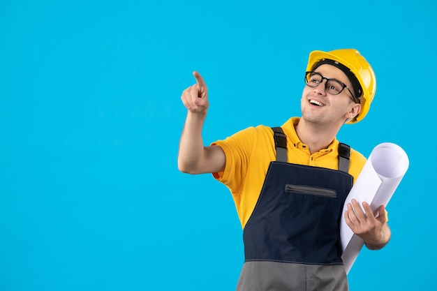 Construtor masculino de vista frontal de uniforme com plano de papel em azul