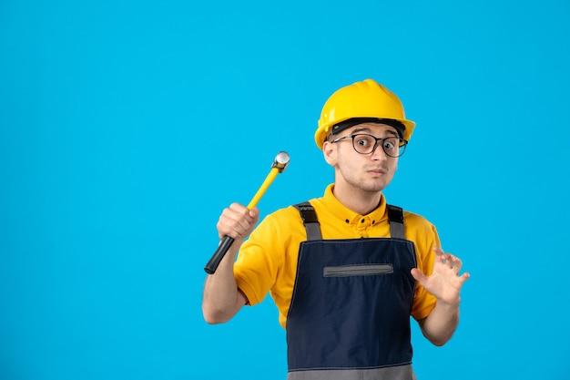 Construtor masculino de vista frontal de uniforme e capacete com martelo em azul